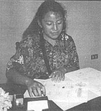 Elizabeth Aju de Tómas signing incorporation papers for FUNDAMARCOS